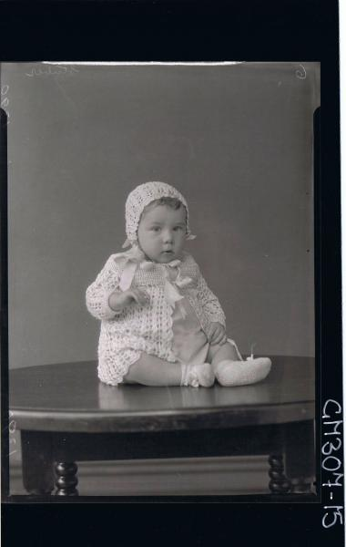 F/L Portrait of baby seated on table wearing cardigan, booties, bonnet; 'Stuber'