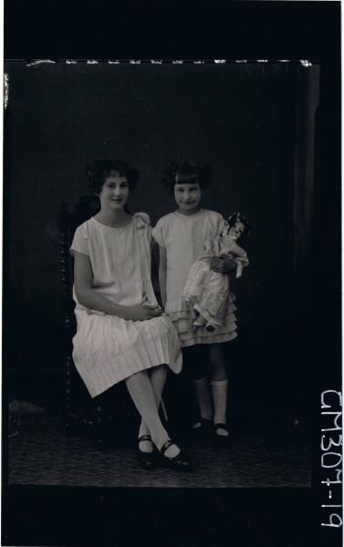F/L Portrait of woman standing wearing knee length dress, girl standing, short dress with 5 tiers holding doll; 'Slater'