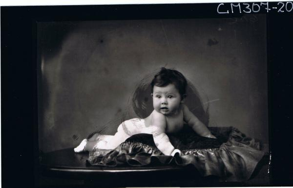F/L Portrait of naked baby lying on table; 'Smith'