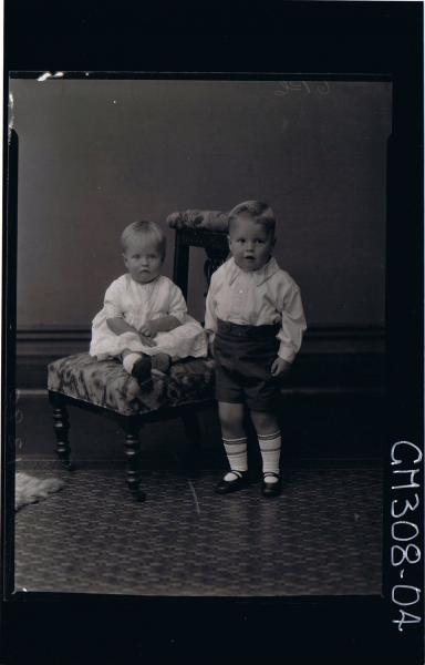 F/L Portrait of boy child standing, wearing shorts, shirt, girl child seated, wearing short lace dress; 'Smith'