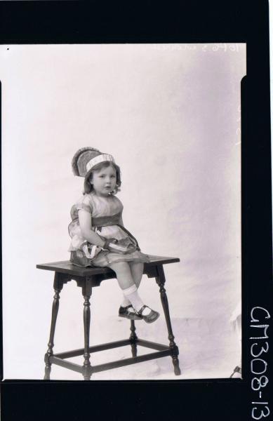 F/L Portrait of small girl seated wearing fancy dress costume, words on hat read 'Rainbow' 'Suckcliffe'