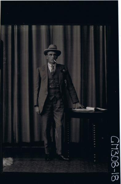 F/L Portrait of man standing wearing three piece suit, cigarette in mouth; 'Skelt'