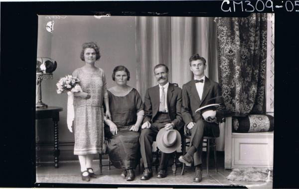 F/L Group Portrait of elderly and young man seated, elderly lady seated, young woman standing with bouquet roses; 'Sain'