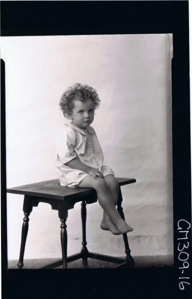 F/L Portrait of child seated on table wearing shirt; 'O'Dea'