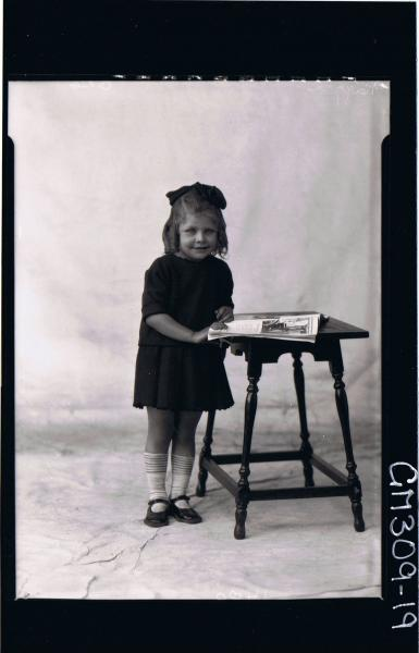 F/L Portrait of girl child standing beside table with book, wearing short dress, ribbon in hair; 'Naggri'