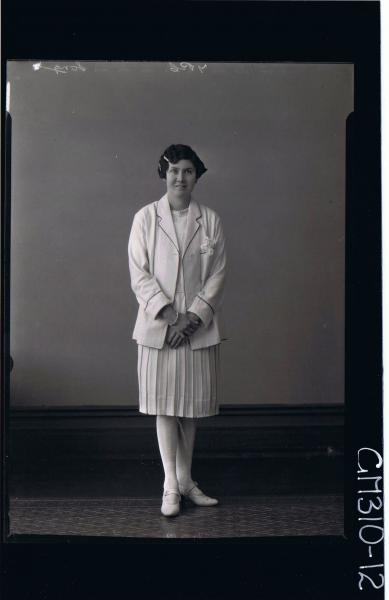 F/L Portrait of woman standing, wearing knee length pleated dress and jacket; 'Song'