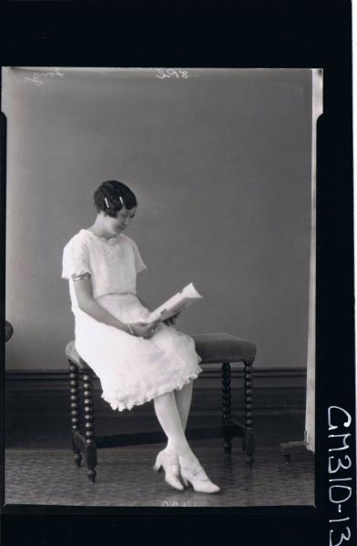 F/L Portrait of woman seated reading a book, wearing knee length lace dress; 'Song'