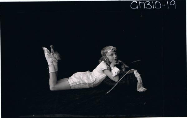 F/L Portrait of girl lying on floor wearing fancy dress costume, arranged for photographs; 'McLeod'