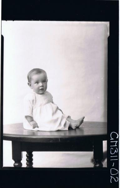 F/L Portrait of baby seated on table, wearing long dress; 'O'Dea'