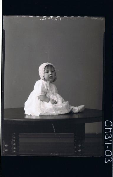 F/L Portrait of baby seated on table wearing lace dress, booties and bonnet; 'Markham'