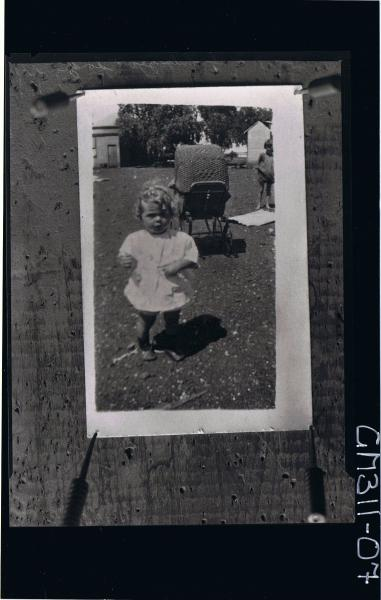 F/L Portrait of child standing in garden in front of a pram,, house and toilet buildings in bgrd; 'Long'