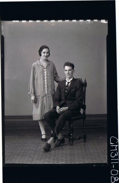 F/L Portrait of man seated wearing suit, woman standing wearing knee length day dress; 'McQuoid'