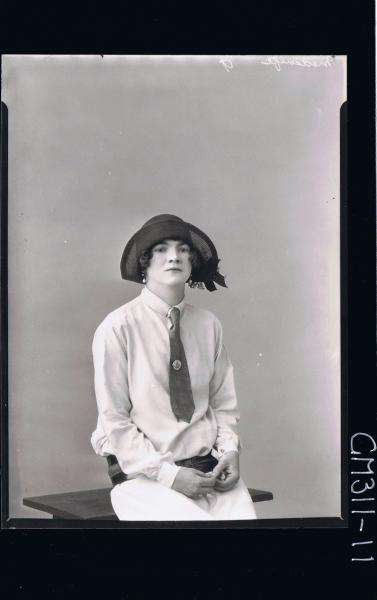 1/2 Portrait of teenage girl seated wearing dress with tie, thick belt around hips also wearing a hat; 'Medcalfe'