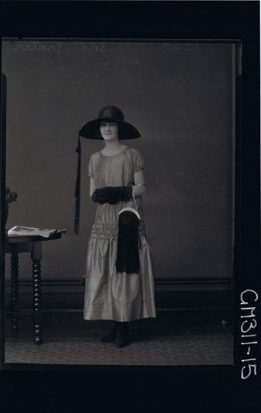 F/L Portrait of woman standing wearing ankle length satin dress, hat, gloves, handbag over arm 'Trotters'