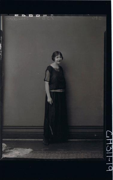 F/L Portrait of woman standing, wearing ankle length dress with sash around hips 'Saunders'