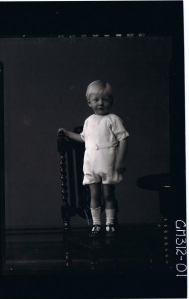 F/L Portrait of boy child standing on chair, wearing one piece shorts and shirt 'Thornton'