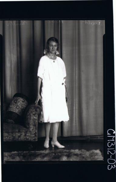 F/L Portrait of woman standing wearing knee length dress, ribbon in hair 'Winter'