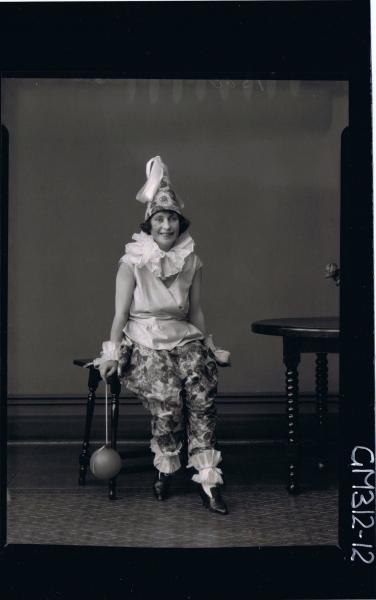 F/L Portrait of woman seated, wearing clown fancy dress costume, holding balloon on string 'Slee'