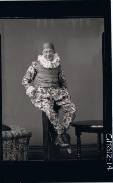 F/L Portrait of man seated on pillar wearing clown fancy dress costume 'Smith'