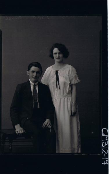 3/4 Portrait of teenage boy seated, wearing suit, young woman standing  3/4 length dress, spectacles 'Small'
