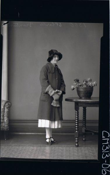 F/L Portrait of woman standing wearing 3/4 length dress,knee length coat, hat, woolly gloves with large cuffs 'Trantum'