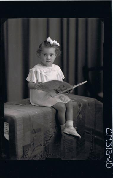 F/L Portrait of girl child seated, wearing short dress, ribbon in hair holding a book 'Cerinich'