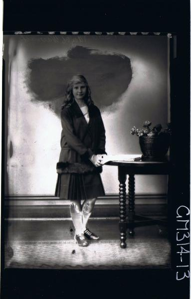 F/L Portrait of girl standing wearing knee length pleated skirt, jacket with fur cuffs & hem 'Warrack'