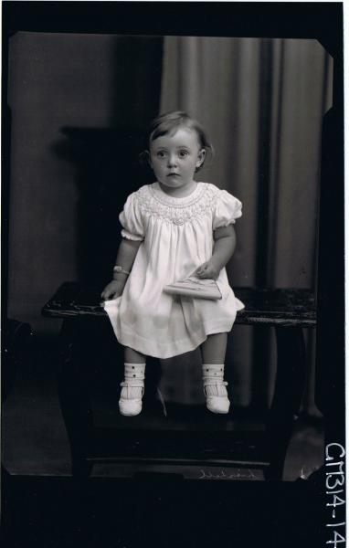 F/L Portrait of girl child seated on table, wearing three quarter length dress, holding bag 'Lischell'
