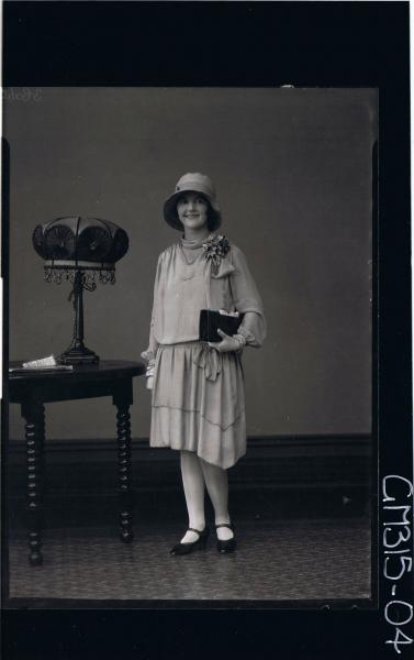 F/L Portrait of woman standing wearing knee length dress, corsage, hat and holding handbag 'Michell'