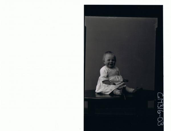 F/L Portrait of baby seated on table wearing dress 'McKay'