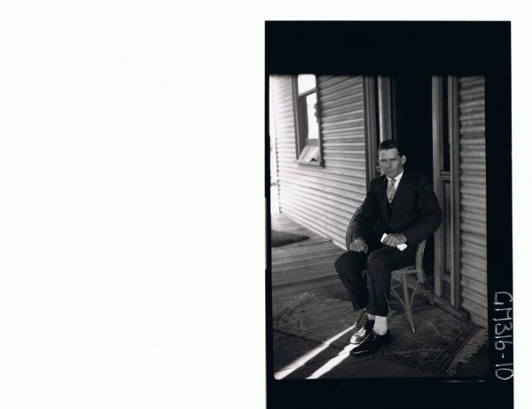 F/L Portrait of man wearing three piece suit, seated on verandah in front of house 'Moore'