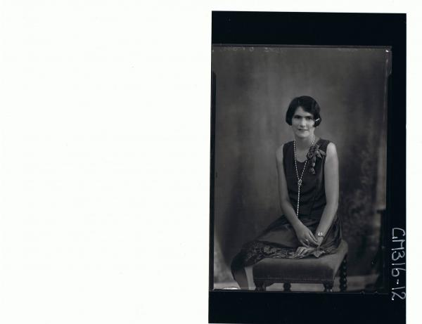 3/4 Portrait of woman seated wearing knee length evening dress 'McCrae'