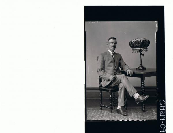 F/L Portrait of man seated at table wearing suit; 'Nisich'