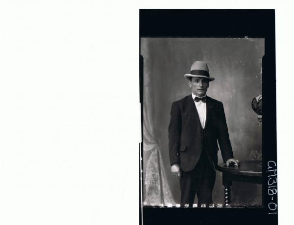 3/4 Portrait of man standing wearing suit, bow tie, hat; 'Nouchey'