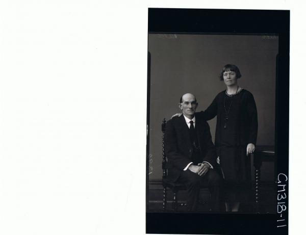 3/4 Portrait of man seated, wearing three piece suit, woman standing wearing 3/4 length dress; 'Scriens'
