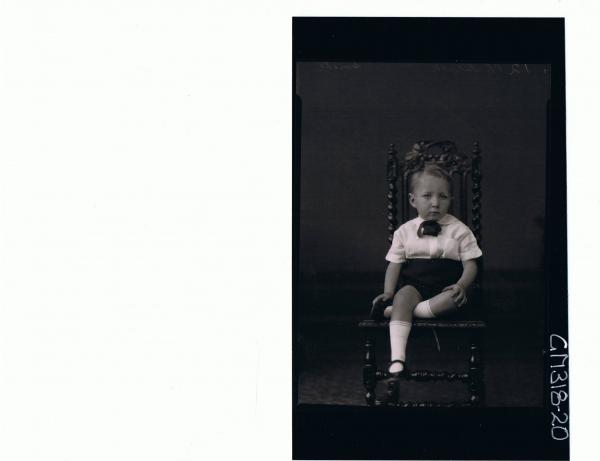 F/L Portrait of boy child, seated, wearing shorts & shirt 'Smith'