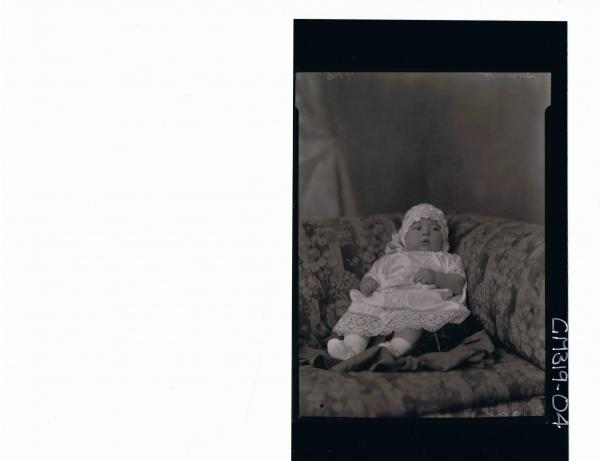 F/L Portrait of baby seated wearing lace christening gown and bonnet 'Summer'