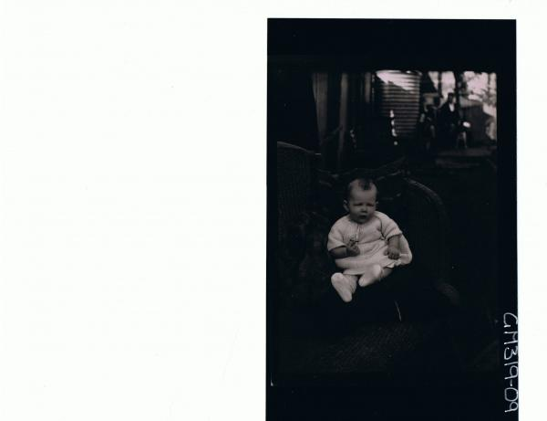 F/L Portrait of baby seated in garden with water tanks and buildings in bgrd. 'Smith'