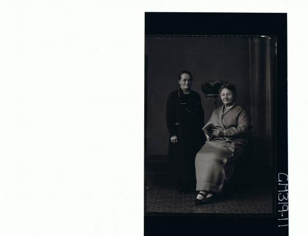 F/L Portrait of elderly lady seated, holding book, elderly woman standing wearing ankle length dress,spectacles'Shocker'