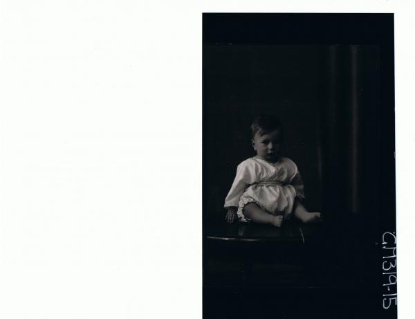 F/L Portrait of baby seated on table wearing overalls 'St Rauch'