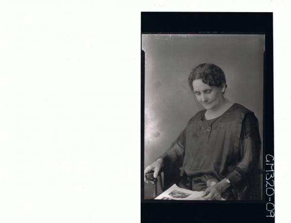 1/2 Portrait of elderly lady seated, looking at book 'Smith'