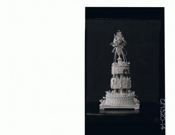 Portrait of three tier wedding cake with vase on top filled with imitation flowers,ribbons hanging down sides'Spalholtz'