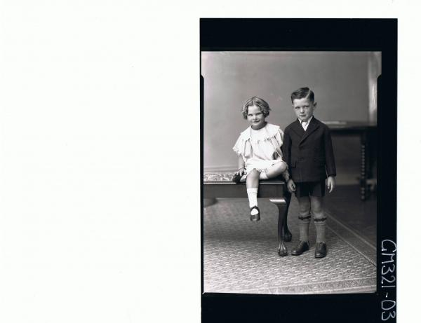F/L Portrait of boy standing wearing shorts, shirt, tie and jacket, girl seated wearing short lace dress; 'Mullins'