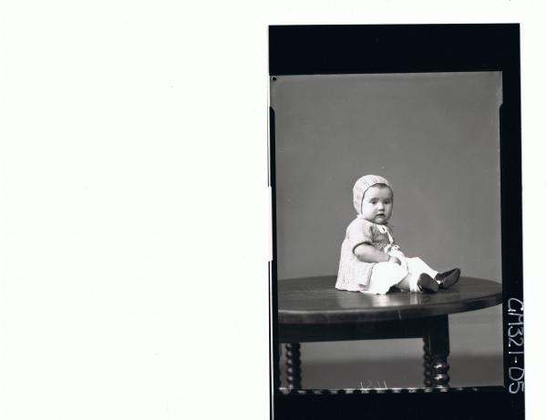 F/L Portrait of baby seated on table, wearing dress, knitted jacket and bonnet; 'Marquano'