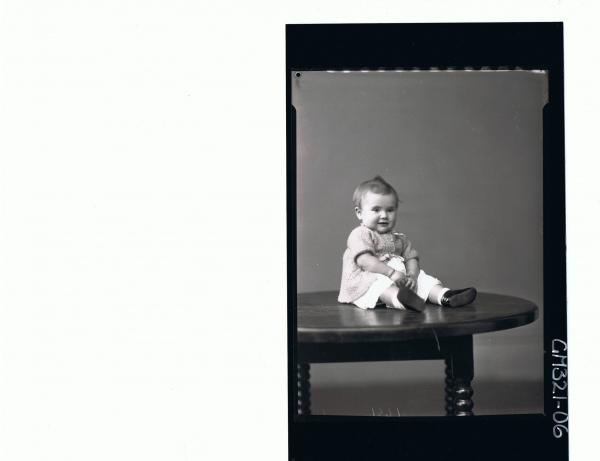 F/L Portrait of baby seated on table, wearing dress, knitted jacket; 'Marquano'