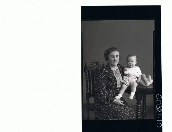 3/4 Portrait of woman seated wearing floral day dress, baby & teddy bear on table wearing shorts, shirt; 'Mitchell'
