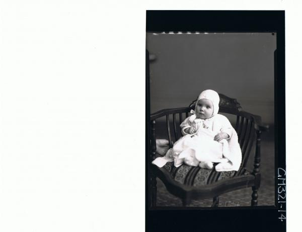 F/L Portrait of baby seated wearing dress, knitted jacket and bonnet; 'Madill'