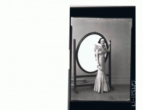 F/L Portrait of woman standing in front of mirror in long evening dress with frills at top & flares at bottom; 'Mills'