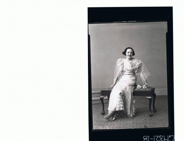 F/L Portrait of woman seated wearing long frilly evening dress; 'Mills'