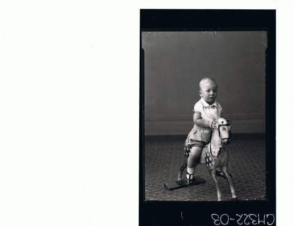 F/L Portrait of child seated on wooden horse, wearing shorts and shirt; 'McQuoid'